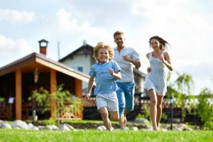 family happily running with house at the background