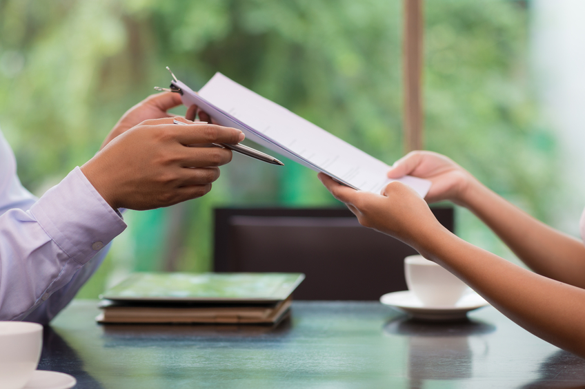Hand of businessman giving document to his female colleague